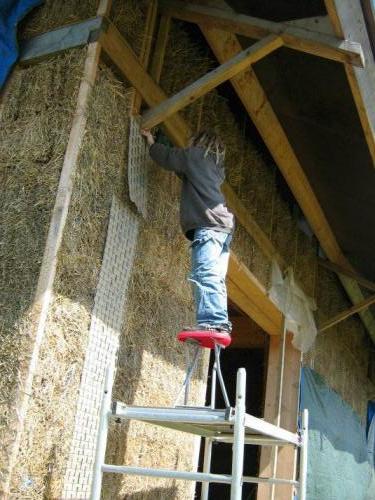 Stro stapelenAan de buitenkant hebben we kippengaas gedaan om het stucwerk beter grip te geven en schuren te beperken.
