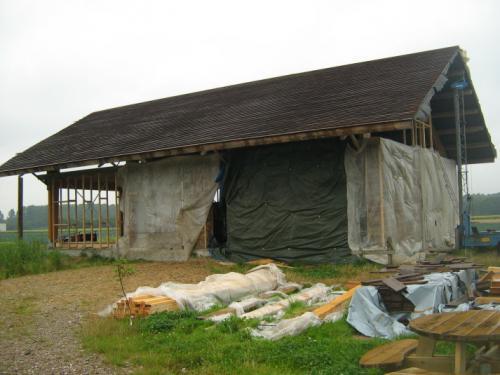 Stro stapelenHet huis was in de wintermaanden ingepakt in het platic om te beschermen tegen de regen en het vocht.